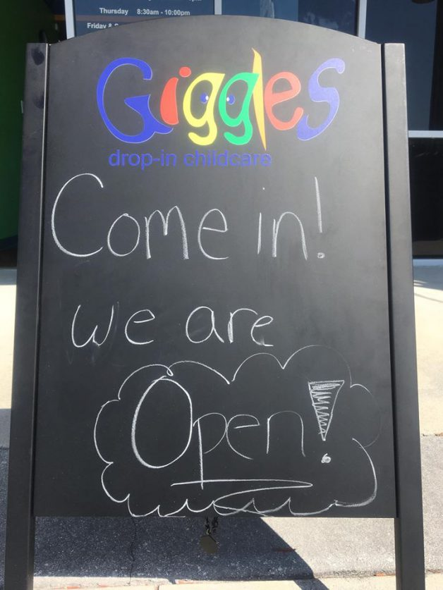 a sign saying that Giggles Drop-In Childcare is now open